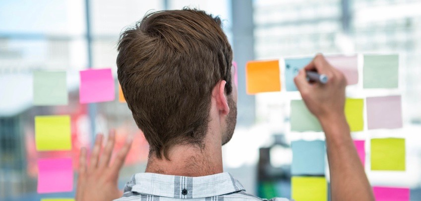man-taking-notes-on-post-its-wall.jpg